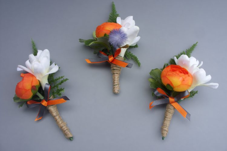 Buttonhole - Orange Ranunculus, Tuberose, backed with Asparagus Fern. Decorated with twine and orange & grey ribbon bow - from £6.00 each