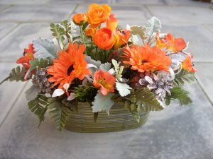 Graveside Arrangement - Orange Runucular, Astromeria and Orange Gerbera, in a Jorvik tin trough with Leather Leaf and Dusty Miller foliage - £42.00